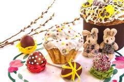 与蛋糕、滑稽的玩具兔子和鸡蛋的复活节构成 免版税库存照片