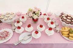 与蛋糕和草莓的甜婚礼表在上面、果子和花 免版税库存图片
