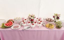 与蛋糕和草莓的甜婚礼表在上面、果子和花 库存图片