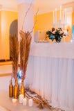 与蛋糕和蜡烛的创造性的婚礼桌 免版税库存照片