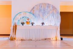 与蛋糕和蜡烛的创造性的婚礼桌 免版税库存图片