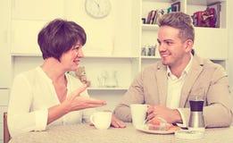 与蛋糕的妇女和人饮用的茶 免版税库存照片