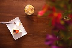 与蛋糕的抽象背景用草莓和冷的咖啡在一张木桌上的 库存图片