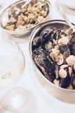 与蛤蜊和水手淡菜的盘与一杯白色藤 免版税图库摄影