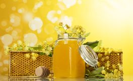 与蜂窝和瓶子的木制框架在黄色背景的蜂蜜 库存照片