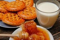 与蜂窝的蜂蜜在一块白色陶瓷板材、曲奇饼用果酱和杯子牛奶 库存图片