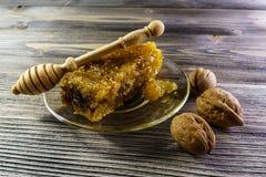 与蜂窝的蜂蜜在老木桌上的一块玻璃板 免版税库存图片