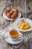与蜂蜜和蛋糕油炸圈饼的茶在木桌上 免版税库存照片