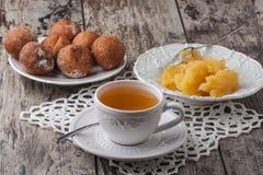 与蜂蜜和蛋糕油炸圈饼的茶在木桌上 免版税库存图片