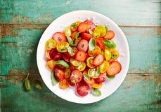 与蜂蜜柠檬选矿和蓬蒿的混杂的西红柿和草莓沙拉 免版税库存照片