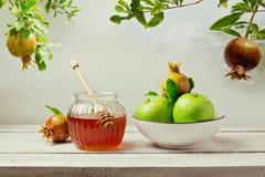 与蜂蜜瓶子、苹果和石榴树的犹太假日Rosh Hashana (新年)背景 免版税库存照片