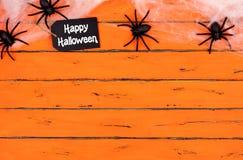 与蜘蛛网上面边界的愉快的万圣夜标记在橙色木头 库存图片