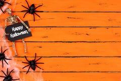 与蜘蛛网边边界的愉快的万圣夜标记在橙色木头 免版税图库摄影