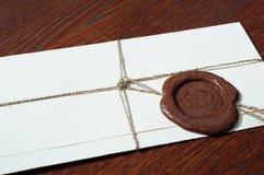 与蜡封印的信封在一张木桌上 库存图片
