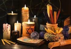 与蜡烛、书和占卜用的纸牌的不可思议的静物画 库存照片