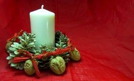 与蜡烛、杉木锥体和坚果的圣诞节装饰在红色背景 复制可利用的空间 对xmas概念 免版税图库摄影