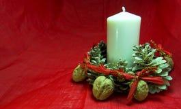 与蜡烛、杉木锥体和坚果的圣诞节装饰在红色背景 复制可利用的空间 对xmas概念 免版税库存图片