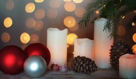 与蜡烛、锥体和欢乐球的静物画在一本圣诞树和诗歌选旁边在背景中 免版税库存照片