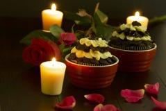 与蜡烛光的巧克力杯形蛋糕 免版税库存图片