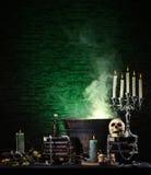 与蜡烛和一块人的头骨的黑暗的背景 免版税库存图片