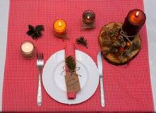 与蜡烛和板材的欢乐构成 装饰餐巾牌照表 一个美好的桌设置,红色桌布,在箱子的桌布 免版税图库摄影