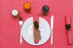 与蜡烛和板材的欢乐构成 装饰餐巾牌照表 一个美好的桌设置,红色桌布,在箱子的桌布 库存照片
