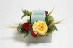 与蜡烛和玫瑰的表植物布置 免版税库存照片