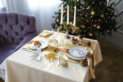 与蜡烛和白色桌布的装饰的桌在一棵装饰的圣诞树的背景 免版税库存照片
