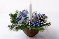 与蜡烛和蓝色丝绸一品红的圣诞节装饰 免版税库存照片