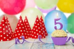 与蜡烛数量上5形状的杯形蛋糕 免版税库存照片