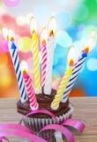 与蜡烛的一块生日杯形蛋糕 免版税库存照片