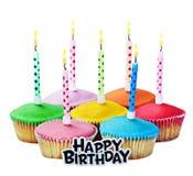 与蜡烛的五颜六色的生日快乐杯形蛋糕 图库摄影