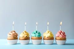 与蜡烛的可口生日杯形蛋糕在轻的背景 库存图片
