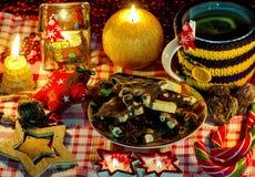 与蜡烛的圣诞节安排,与坚果,巧克力块,茴香的巧克力担任主角,干茶,装饰,蜡烛,糖果 免版税库存图片