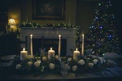 与蜡烛的圣诞节桌植物布置 免版税库存图片