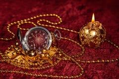 与蜡烛的圣诞节静物画和在伯根地背景的怀表 免版税图库摄影