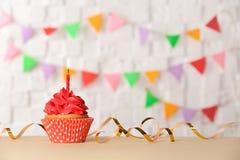 与蜡烛的生日杯形蛋糕反对背景 库存照片