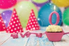 与蜡烛的生日杯形蛋糕在上面 图库摄影