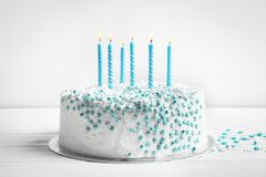 与蜡烛的生日蛋糕在桌上对墙壁 免版税库存图片