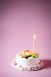 与蜡烛的生日蛋糕在颜色背景 库存图片