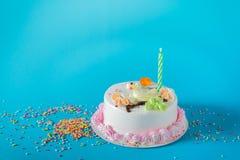 与蜡烛的生日蛋糕在颜色背景 图库摄影