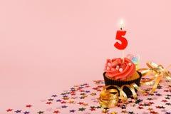 与蜡烛的第五块生日杯形蛋糕和洒 免版税库存图片