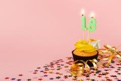 与蜡烛的第十八块生日杯形蛋糕和洒 免版税库存照片