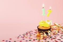 与蜡烛的第17块生日杯形蛋糕和洒 库存照片
