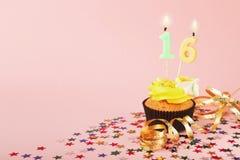 与蜡烛的第16块生日杯形蛋糕和洒 免版税图库摄影