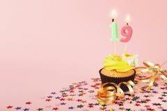 与蜡烛的第19块生日杯形蛋糕和洒 库存图片