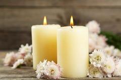 与蜡烛的美丽的白色菊花在灰色木背景 库存图片