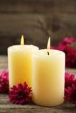 与蜡烛的美丽的紫色菊花在灰色木背景 图库摄影