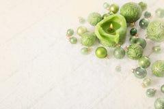 与蜡烛的绿色白色多雪的背景 免版税库存图片