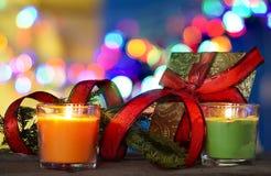 与蜡烛,红色丝带和礼物盒的圣诞节装饰,在defocused背景下 免版税库存照片